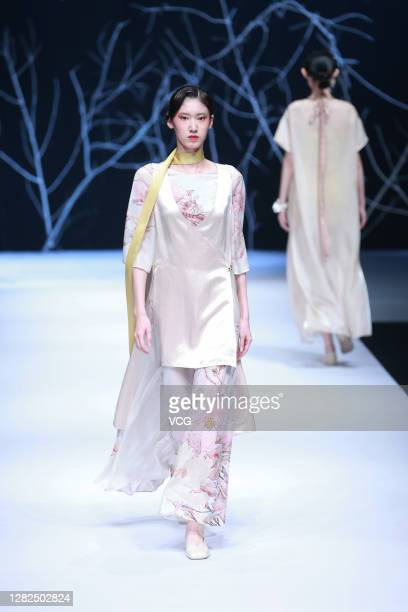 A model showcases designs on the runway during Rongwujie collection show by designer Xiao Hua on day 3 of China Fashion Week 2021 Spring/Summer at...