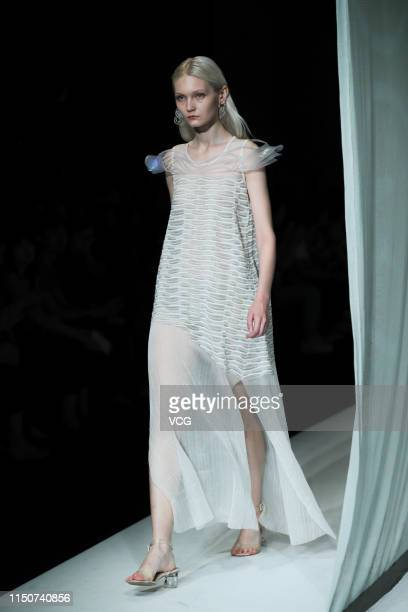 A model showcases designs on the runway during the Academy of Arts Design of Tsinghua University show on day seven of China International College...