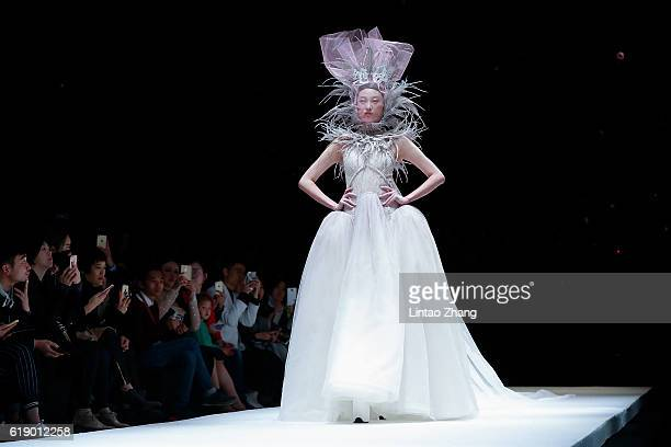 A model showcases designs on the runway during the JUSERE series by Chinese designers Qiying Wei wedding dress conference show during MercedesBenz...