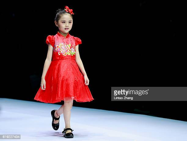 A model showcases designs on the runway during the Parentchild release conference by Chinese designer Wangxiaohe and Yong Fan during MercedesBenz...