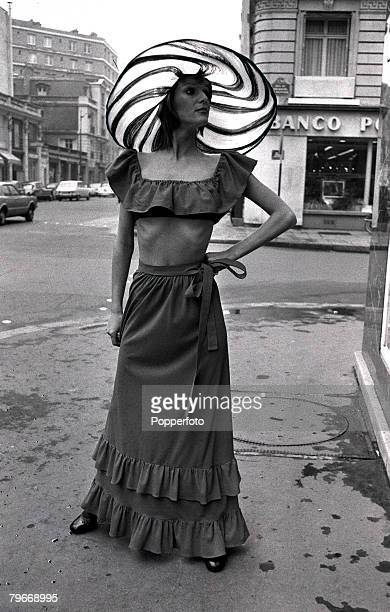 A Model shows a red nylon crepe beach ensemble worn with a large brimmed hat part of the Torrente readytowear summer collection 23rd January 1972