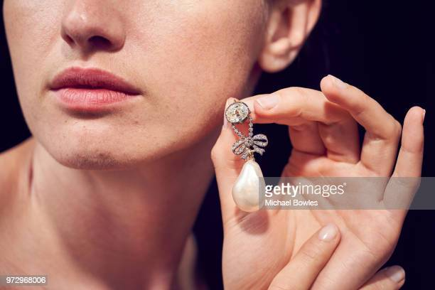 A model shows a stunning diamond pendant supporting a natural pearl of exceptional size that belonged to MarieAntoinette Queen of France and will be...