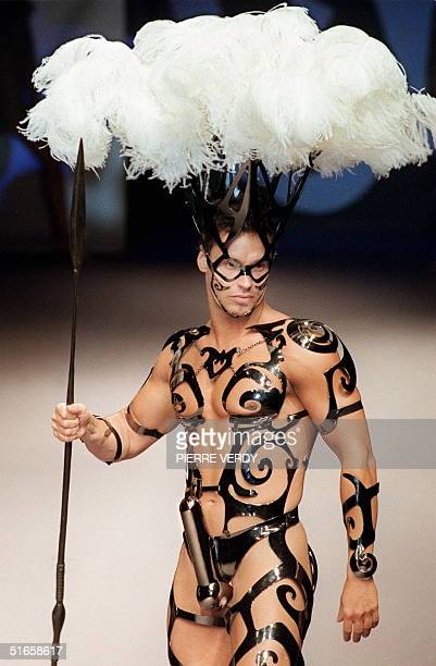 A model shows off 21 January a metallic Maoritype tattoo sculpture wedding outfit with white ostrich feather headgear during the presentation of Paco...