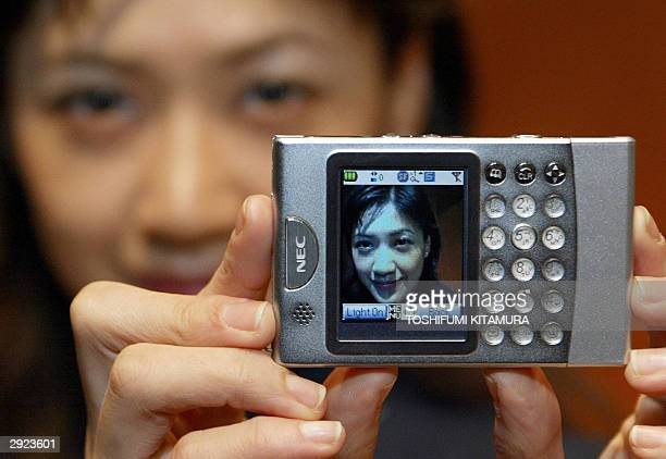A model shows off NEC's world's smallest slimmest cardshaped cameraequipped mobile phone during its press preview in Tokyo 03 February 2004 The...