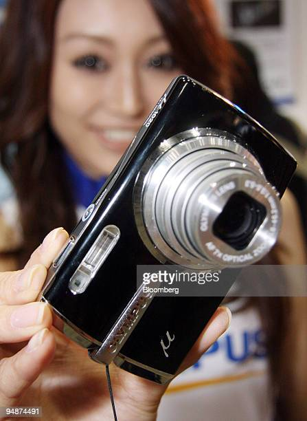 A model shows off Olympus Corp's 1020 digital camera at the Photo Imaging Expo in Tokyo Japan on Wednesday March 19 2008 Olympus Corp is the world's...