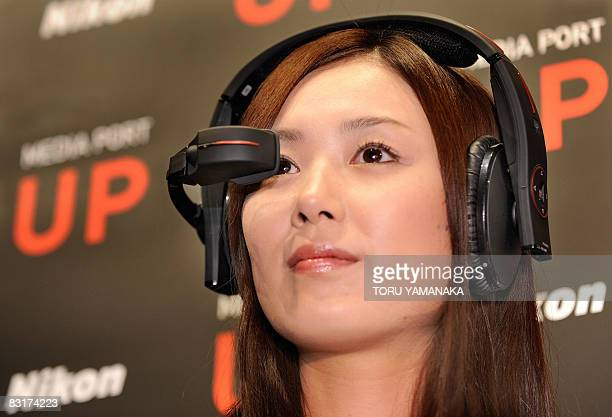 A model shows off the new headmounted display UP of Japan's camera maker Nikon during a press preview in Tokyo on October 7 2008 Nikon will release...
