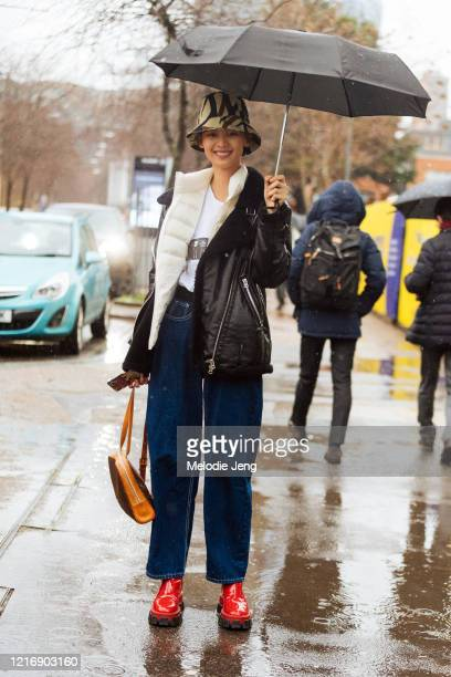 Model Shuping Li carries an umbrella and wears a camouflage bucket hat, black leather shearling jacket, blue jeans, and red Prada rain boots after...