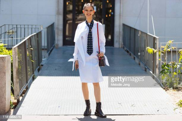 Model Shuping Li wears a white shirt dress, tie, brown bag, and black boots after the Elie Saab show during Couture Fashion Week Fall/Winter 2019 on...