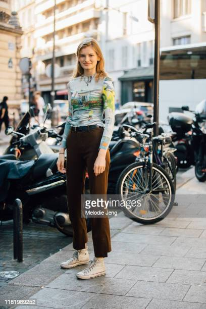Model Signe Veiteberg wears a green graphic shirt, brown pants, and white Converse sneakers during Couture Fashion Week Fall/Winter 2019 on July 03,...