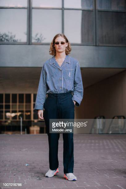 Model Simon Fakkert wears a blue striped YSL shirt blue pants and Nike sneakers during New York Fashion Week Men's Spring/Summer 2019 on July 9 2018...