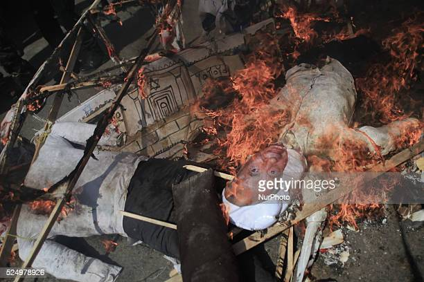A model simulation for the President of Israeli government Shimon Peres is burning after Palestinians masked of Hamas burned it during a rally...