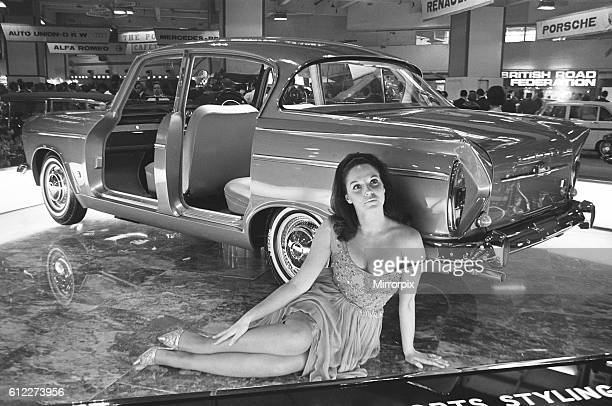 Model sits beside a Humber car at the British International Motor Show in London 19th October 1965