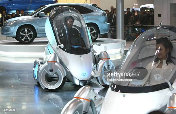 Model sits in a cockpit of Toyota's new concept car the 'PM' during the 37th Tokyo Motor Show at Makuhari Messe, east of Tokyo October 22, 2003 in...