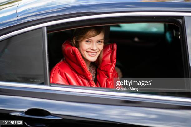 A model sitting in a car wearing red down feather jacket is seen outside Sacai during Paris Fashion Week Womenswear Spring/Summer 2019 on October 1...
