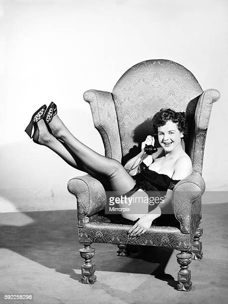 Model sitting in armchair with telephone E144005