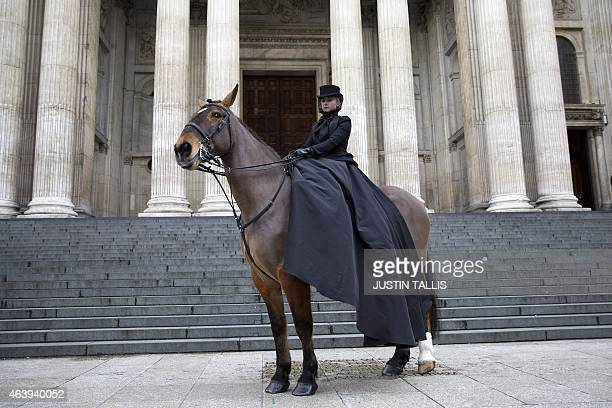A model sitting on a horse wearing a black top hat veil jacket and trailing skirt by Sarah Burton for Alexander McQueen is pictured outside St Paul's...