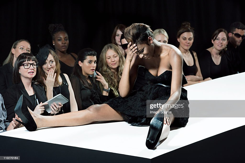 Model sitting on catwalk having fallen down at fashion show : Bildbanksbilder