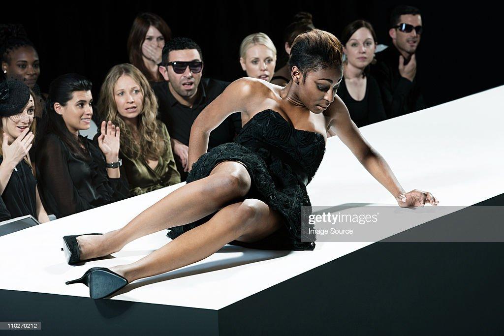 Model sitting on catwalk having fallen down at fashion show : Bildbanksbilder