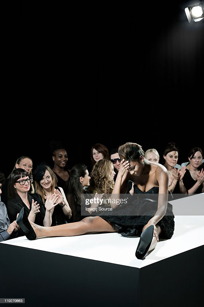 Model sitting on catwalk having fallen down at fashion show : Stock Photo