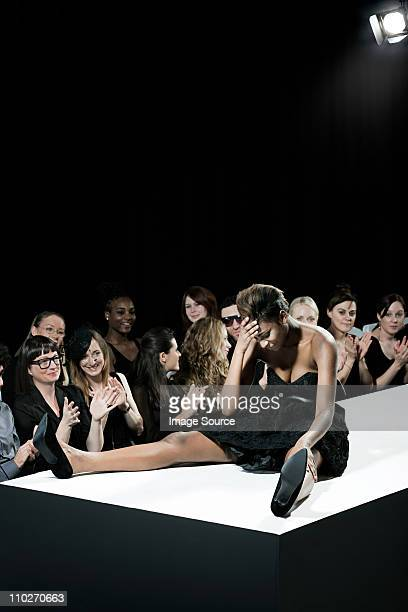 model sitting on catwalk having fallen down at fashion show - catwalk model stock photos and pictures