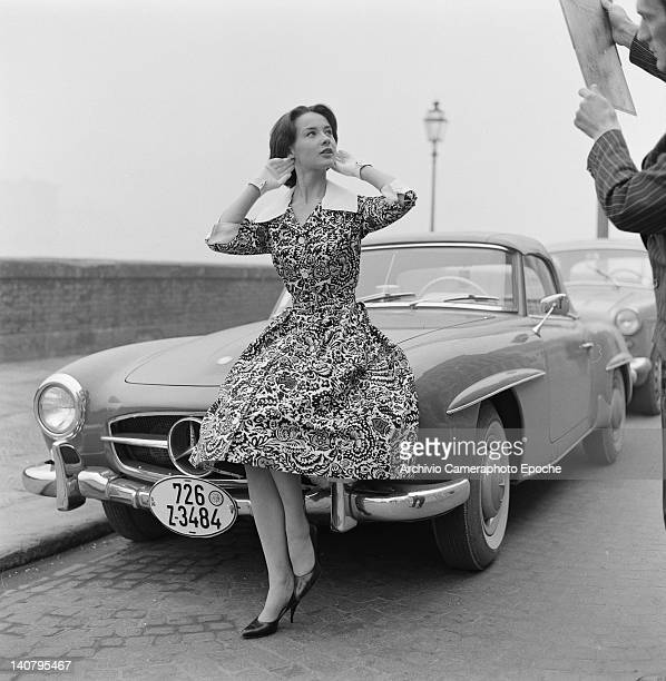 A model sitting on the bonnet of a MercedesBenz 190SL roadster as a photographer's assistant holds up a reflector Italy circa 1955 The woman is...