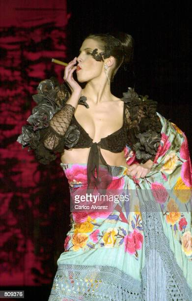 A model smokes a cigar as he wears a design from the Montesinos Alama Fall/Winter 2001 collection February 19 2001 on the third day of Cibeles...