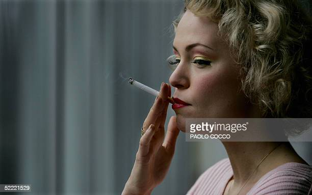 Model smokes a cigarette as she waits for displayng a collection during Milan's fashion week, 20 February 2005. AFP PHOTO/ Paolo COCCO