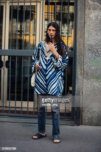 A model smoking a pipe during Milan Men's Fashion Week Spring/Summer 2019 on June 16 2018 in Milan Italy