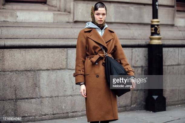 Model Sofa Pletneva wears a floral headscarf, brown belted bag, and black bag after the Erdem show during London Fashion Week February 2020 on...