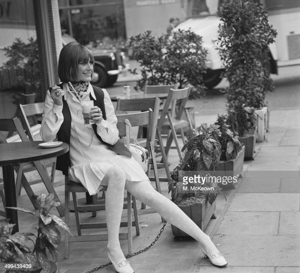 Model Sonya Dean wearing a shirt dress and waistcoat by Simon Jeffrey with patterned white tights by Mary Quant and white Corform shoes by Russell...