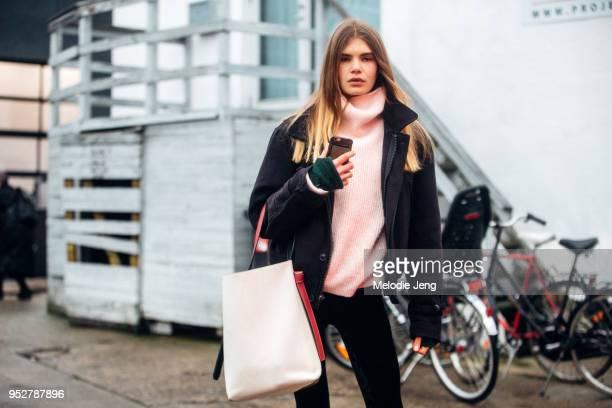 Model Sophie Rask wears a cropped black jacket yellow turtleneck oversized sweater and a Celine bag at Copenhagen Fashion Week Autumn/Winter 18 on...