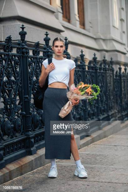 Model Sophie Rask wears a cropped white top gray skirt white sneakers and holds a bouquet of flowers during New York Fashion Week Spring/Summer 2019...