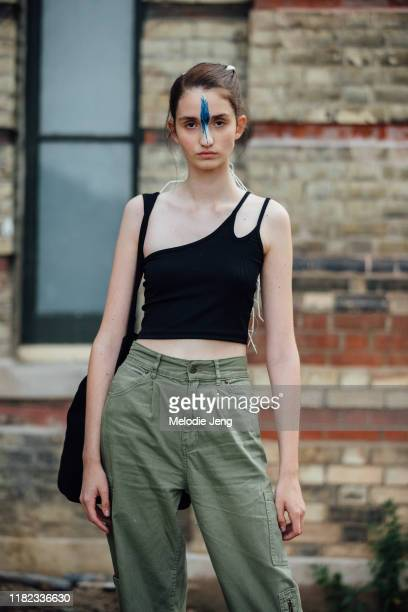 Model Sophie Schonauer after the Simone Rocha show with a hand painted feather makeup on her face by Thomas de Kluyver black singleshoulder tanktop...