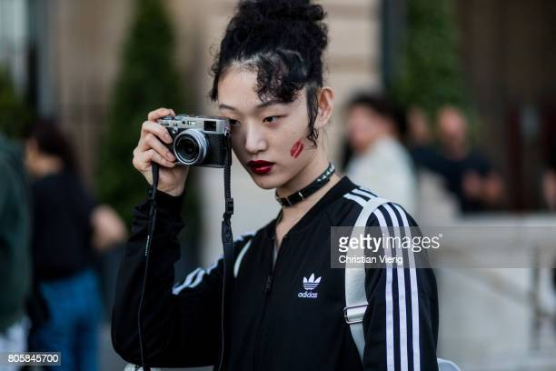 Model Sora Choi with her camera outside Miu Miu Cruise Collection during Paris Fashion Week Haute Couture Fall/Winter 20172018 Day One on July 2 2017...