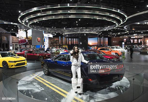 Model stands alongside the 2017 Dodge Challenger display during the 2017 North American International Auto Show in Detroit, Michigan, January 10,...