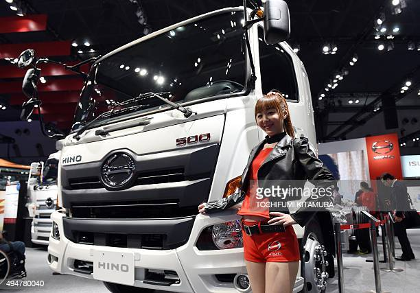 A model stands beside a Hino 500 truck at the Tokyo Motor Show in Tokyo on October 29 2015 The biennial motor show's 44th edition which runs until...