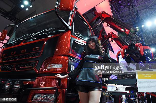 A model stands beside a Mitsubishi Fuso concept Super Great V / Spider at the Tokyo Motor Show in Tokyo on October 29 2015 The biennial motor show's...