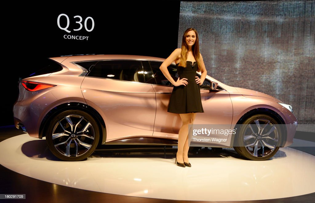 A model stands beside the new Infinity Q30 during the press day at the international motor show IAA (Internationale Automobil-Ausstellung) on September 11, 2013 in Frankfurt am Main, Germany. The world's biggest motor show, the IAA, is running from September 12 to 22, 2013
