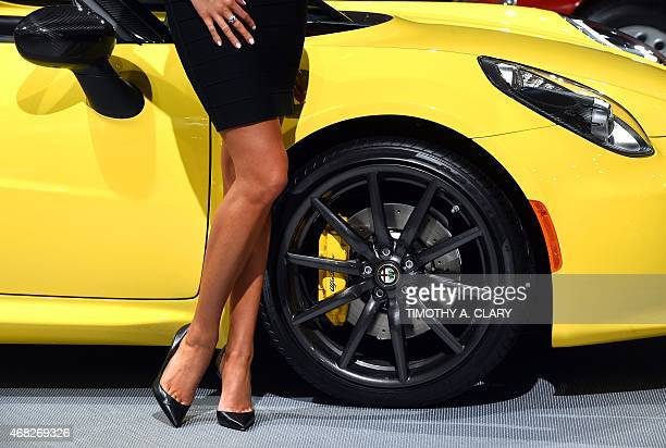 A model stands next to an Alfa Romeo 4C Coupe during the first press preview day at the 2015 New York Auto Show April 1 2015 at the Jacob Javits...