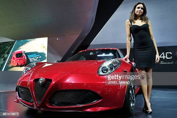 A model stands next to the new Alfa Romeo 4C during the press preview at The North American International Auto Show in Detroit Michigan on January 13...
