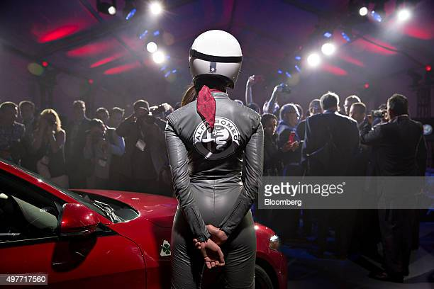 A model stands with a 2017 Alfa Romeo Giulia Quadrifoglio vehicle sits on stage following its North American debut during the Los Angeles Auto Show...