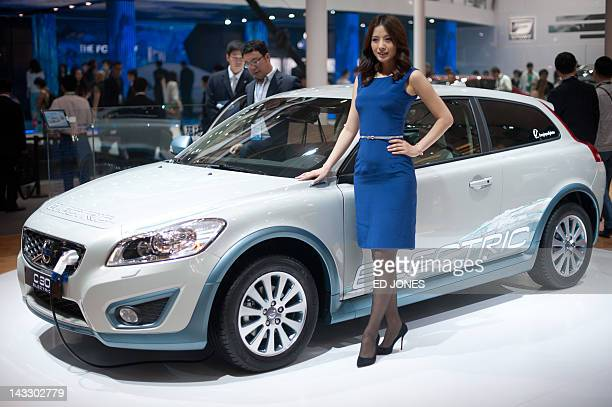 A model stands with a Volvo 'C30' electric car at the Auto China 2012 car show in Beijing on April 23 2012 Beijing is hosting the Auto China 2012...