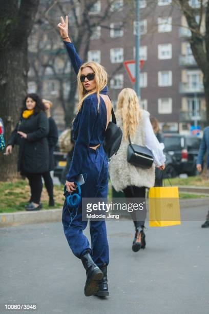 Model Stella Maxwell throws a peace sign and wears black sunglasses, a blue velvet jumpsuit, black Vetements x Dr. Martens Borderline Boots, and...