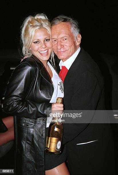 Model Stephanie Heinrich poses with Playboy founder Hugh Hefner at Barfly club for the Barfly Friday Night Christmas Party featuring Playboy...