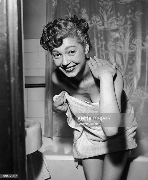 Model steps out of the shower wrapped in a towel, March 1954.