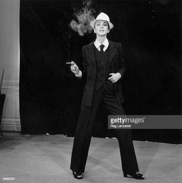 A model strikes a masculine look wearing a pinstriped trouser suit by Yves Saint Laurent His plainer suit for evening wear known as 'Le Smoking'...
