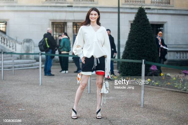 Model Sui He attends the Chloe show in a loose white top blue shorts white Chloe bag and black heels at Grand Palais during Paris Fashion Week...