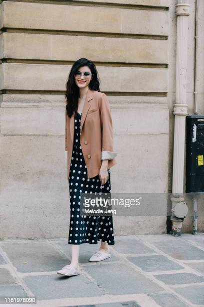 Model Sui He wears a cream blazer, black polka-dot dress, and white jeweled slippers after the Dior show during Couture Fashion Week Fall/Winter 2019...