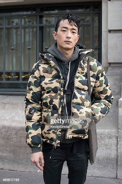 Model Sung Jin Park wears Acne trousers Bathing Ape coat Alexander Wang top and Rick Owens bag day 4 of Paris Mens Fashion Week Autumn/Winter 2014 on...