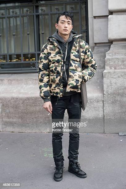 Model Sung Jin Park wears Acne trousers Bathing Ape coat Balenciaga trainers Alexander Wang top and Rick Owens bag day 4 of Paris Mens Fashion Week...